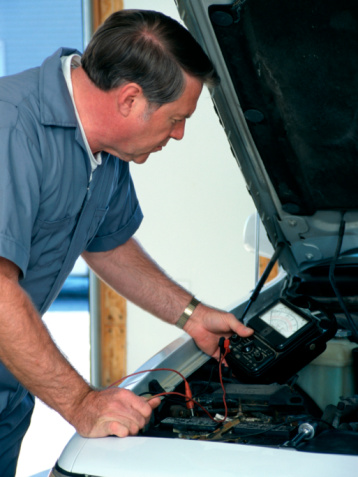 A middle-aged adult Caucasian car mechanic checking a car battery